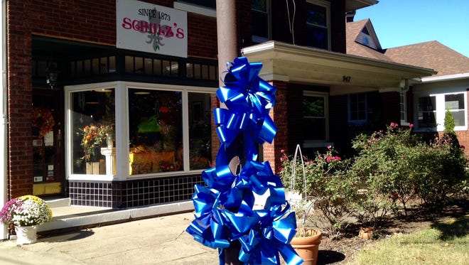 Free blue ribbons in support of law enforcement are displayed on a pole in front of Schulz's florist in Germantown, thanks to a neighborhood donor.