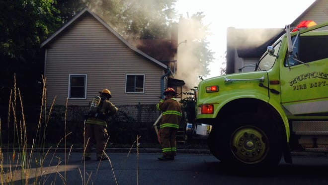 Firefighters enter a burning house at 216 N.  Hackley St. in Muncie.
