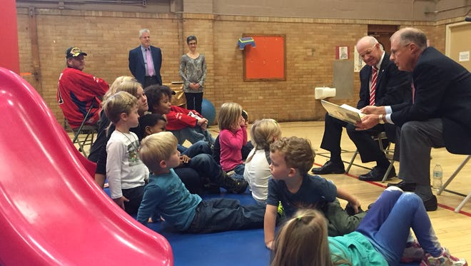 Retired U.S. Army Major General Gerald Miller, left, and retired U.S. Air Force Major General Thomas Culter, right, read to a group of preschoolers at Education Child Care Center in Lansing Tuesday, Nov. 11, 2015.