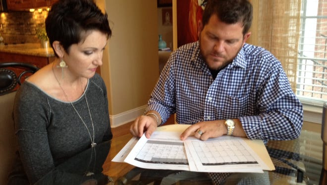 Rachel and Justin Holder go over the bank statements that alerted them to missing funds.