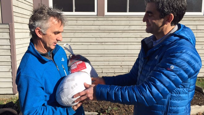 Burlington Mayor Miro Weinberger, right, hands Chittenden Emergency Food Shelf Director Rob Meehan two turkeys he donated for the nonprofit's annual Thanksgiving food drive on Wednesday morning.
