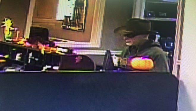 The suspect stands at the counter of Cumberland Bank and Trust on Tuesday.
