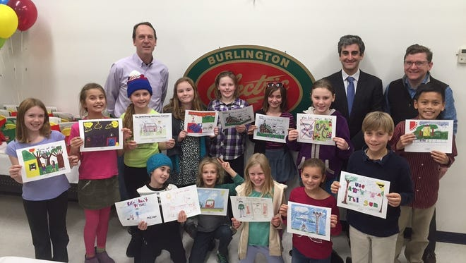 Former Burlington Electric General Manager Mark Stephenson, left, Mayor Miro Weinberger and current BED head Neale Lunderville pose with the winners of the 2016 Energy Efficiency Calendar contest on Thursday at the utility's headquarters on Pine Street.