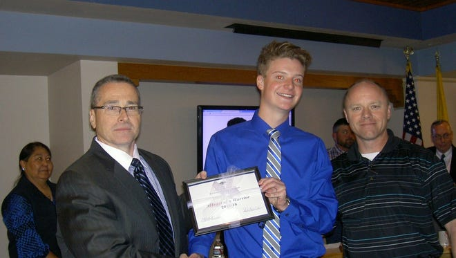 """Ruidoso High School student Landon Taylor receives a """"Heart of a Warrior"""" award from Supt. George Bickert at Tuesday's school board meeting. Taylor was recognized for his outstanding efforts to build RHS school spirit."""