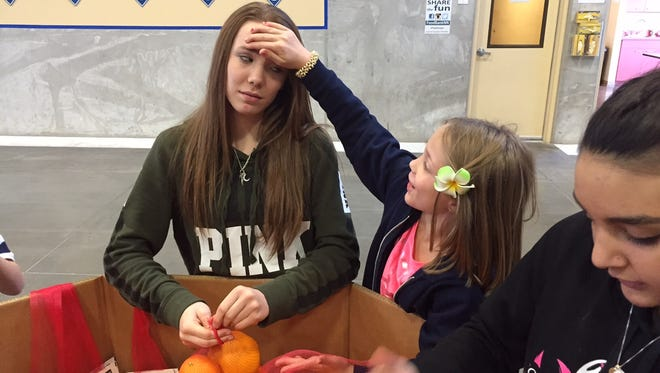 Makayla Linney, 13, and Madison Burns, 7, share a lighthearted moment at the Food Bank of Northern Nevada volunteering event while Callie Hallmark, 13, bags oranges on the right.