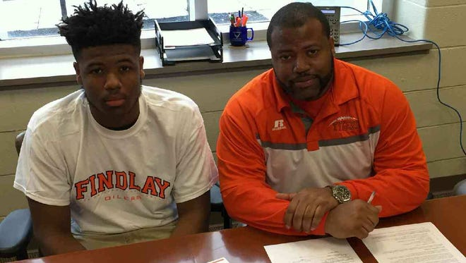 Manasfield Senior football coach Chioke Bradley with his son, Chioke Jr., after signing his national letter of intent to play college football for the University of Findlay, an NCAA Division II team and rival of Ashland University in the Great Lakes Intercollegiate Athletic Conference. Bradley, a tight end, will study computer science in college.