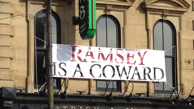 A sign outside of Patrick O'Shea's on Whiskey Row calls U of L President James Ramsey a coward.