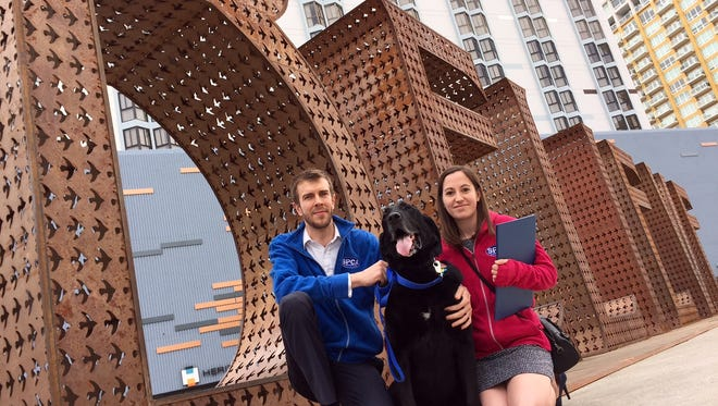"""Robert Stachow and Lisa Rosen pose for a photo with their 5-year-old dog, Everett, on Thursday in front of the """"Believe"""" sculpture in downtown Reno."""