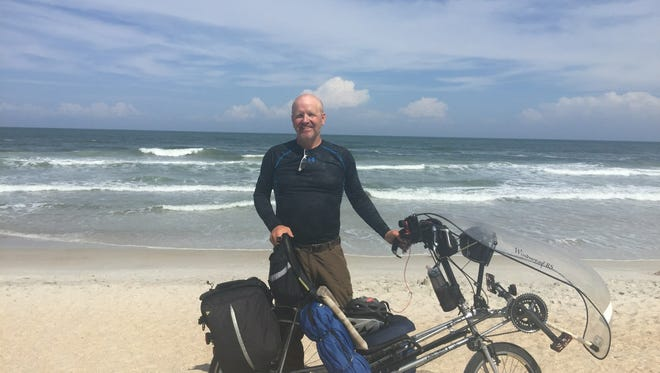 John Williams, of  Warsaw, poses in front of the Atlantic Ocean in St. Augustine, Fla., after riding his bike cross-country from San Diego, Calif.