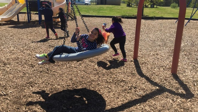 """Children play on the tire swing Saturday morning at North Park during Thelma Barker Elementary School's """"Barker in the Park."""""""