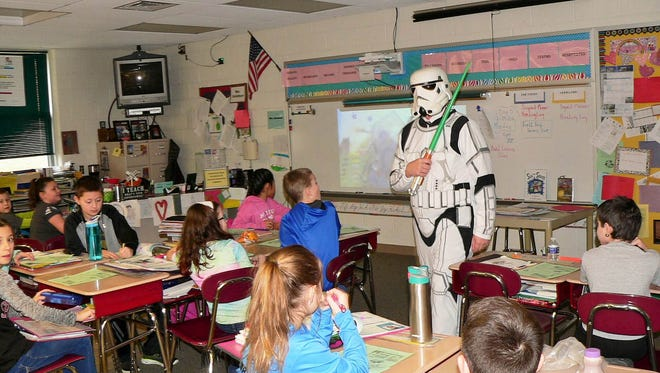 The Read Across America theme at South Lebanon Elementary School, 'Reading is Space-tacular,' was based on the Dr. Seuss book, 'There's No Place Like Space.' To kick off the recent week filled with reading incentive activities, Principal Barry Ferguson, dressed as a stormtrooper from the 'Star Wars' franchise, visits, Maria Schelhorn's fifth-grade class. The stormtrooper also greeted students as they arrived at school and made a special appearance on the morning announcements. The week culminated with the students being treated to a prismatic laser assembly.
