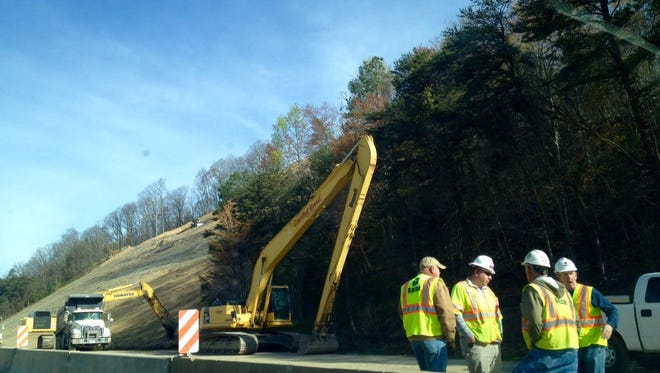 Crews work on clearing the hillside along I-75N in Campell County Tenn., where all lanes are now open.