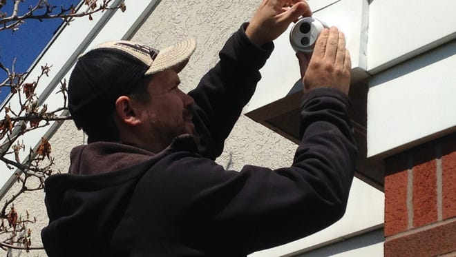 Mark Hoffman, a Crime Intervention Alarm Inc. worker, installs a camera at York Area Regional Police Department,  located at 33 Oak St. in York Township.
