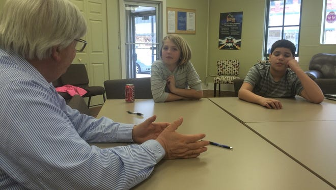 Lexis Krause, left, and Benjamin Roman listen as news editor Warren Bluhm explains the news-gathering process Thursday during Take Your Child to Work Day at the Door County Advocate.