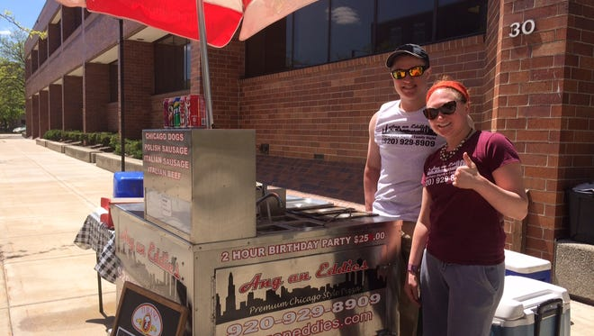 Curtis Marschall and Kayla Waters work Ang an Eddie's hot dog cart, which will set up shop downtown in good weather.
