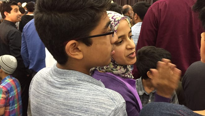 Zaiba Malik and son Jihad Khan, 14, wait for the start of Muhammad Ali's funeral Thursday in Louisville, Ky.