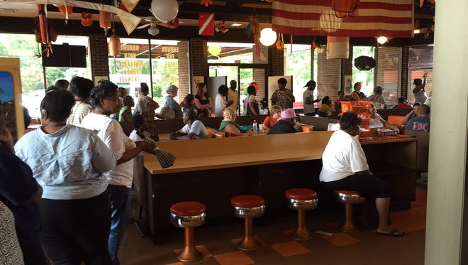 The line at Tanner's Big Orange wrapped around the restaurant Tuesday, as people waited to get their 50-cent hot dogs, drinks and fries.
