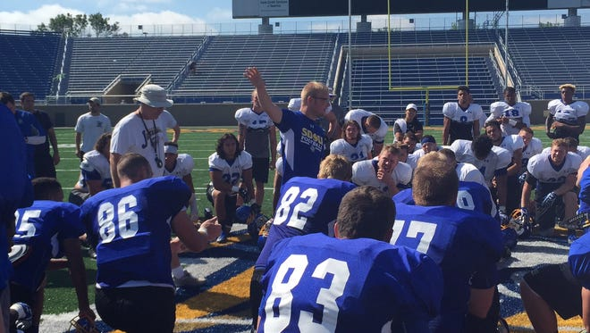SDSU director of operations Adam Satterwhite talks to players after practice while coach John Stiegelmeier looks on
