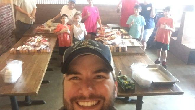 Hook & Boil owner Mark Alleman takes a selfie with volunteers at his restaurant who helped feed flood victims and emergency workers this weekend.