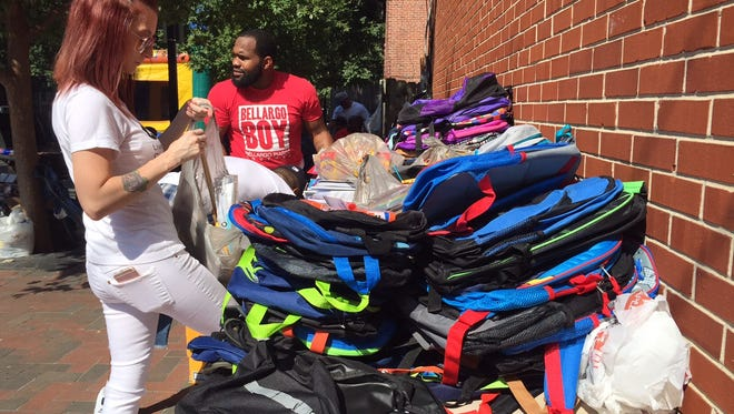 Volunteers sort some of the 1,000 backpacks donated to neighborhood children in Wilmington's East Side.