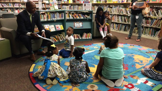 Jackson City Councilman Ernest Brooks II shares his favorite stories with children at the introductory event for Library Card Sign-up Month at the Jackson-Madison County Library.