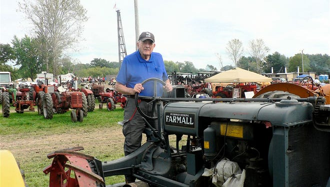 "The writer poses on a Farmall Standard like the one that he learned on, except his dad's was a red color and had different wheels.  He is standing on the platform as he did when plowing to prevent ""eating the steering wheel"" if the plow hit a rock."