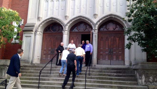 People file up the steps of St. Martin de Porres Catholic Church on West Broadway for Friday evening's peace service led by Louisville Archbishop Joseph Kurtz.
