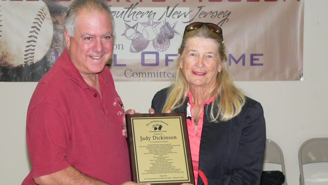 Dom Valella, chairman of the All Sports Museum of Southern New Jersey, presents Judy Dickinson with a plaque during her induction ceremony on Sept. 13.
