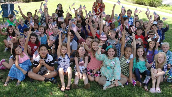 McKenzie Coan, at center in background, poses with third-graders at Toccoa Elementary School.