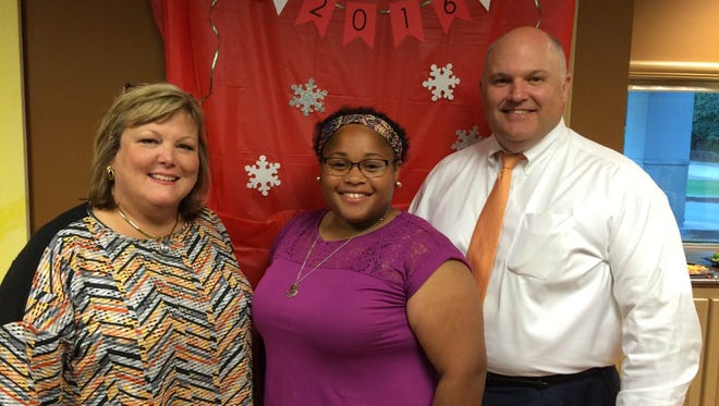Laura Byrd, left, and Charles Byrd, co-chairs for the Jingle Bell Run for Arthritis, stand with Emani Neely, the child honoree of the fundraiser.