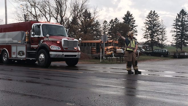 A firefighter directs traffic Monday at the scene of a SUV-school bus crash in Richfield.