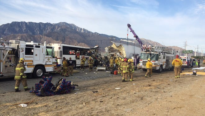 Emergency personnel work to remove victims from a tour bus crash that killed at least 11 people in Palm Springs Oct. 23, 2016. The crash occurred just after 5 a.m. along westbound Interstate 10. About 30 others were hospitalized. A portion of I-10 was shut down.