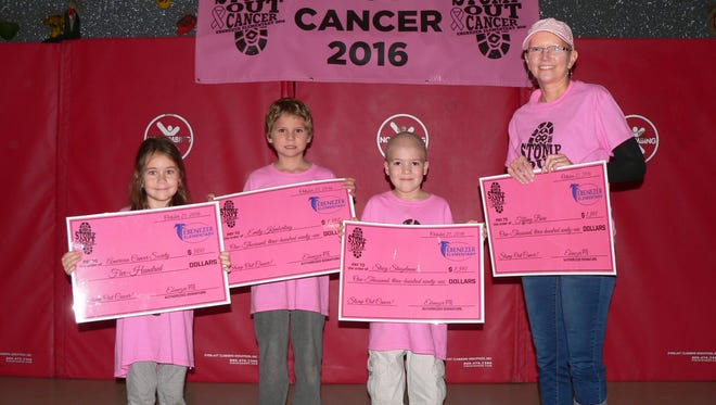 Posing with their checks, from left to right, are cancer survivors Sienna Henning, first grade; Chase Kimberling, first grade; Lucas Stigelman, second grade; and Tiffany Bare.