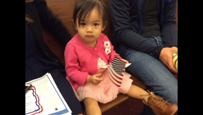 Naomi Y Vu holds one of the small American flags handed out at naturalization ceremonies in York County. Naomi is the daughter of Trang Vu, a new American citizen, originally from Vietnam, who took the oath of allegiance to the U.S. on Thursday. Naomi's father is Andy Vu.