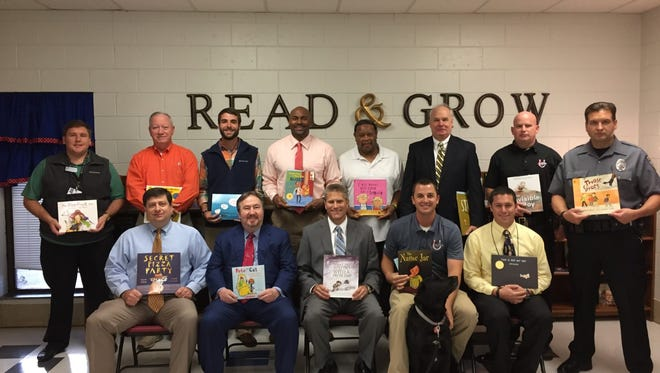 Real Men Readers shown in back row are Wesley Carwile, Doug Atkins, Micah Roberts, Mr. McGowens, Coach Peppers, Mr. Havird, Officer Sargent and Officer Hopkins; and in front row are Mr. Thomas, Dr. Keith, Mr. Binnicker, Mr. Scroggs and Mr. Economou.