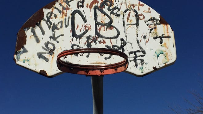 Graffiti covers a corroded backboard on a basketball court at Rev. Evers Park in Camden's Morgan Village neighborhood.