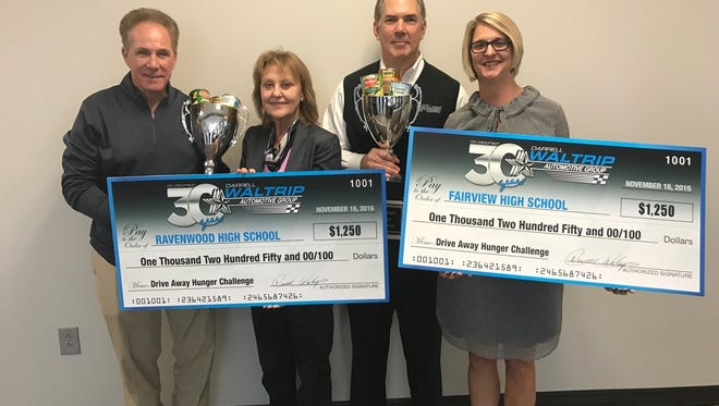 Ravenwood High and Fairview High collected the most food for the annual Drive Away Hunger Challenge. The schools' leadership hold checks of their reward for winning the challenge.
