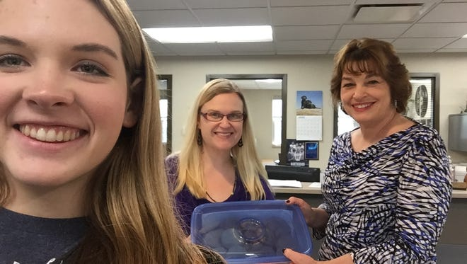 South Lyon High School student Caitlin Kernander (left) took a selfie as she delivered homemade cookies to the Lyon Township staff including planning secretary Katherine DesRochers (center) and deputy clerk April Talaga.