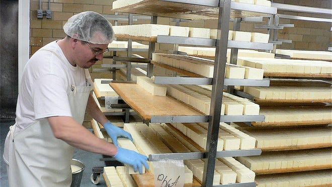 Brian Endresser stacks Limburger on pine boards for curing.