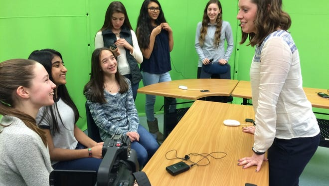 The winning team from Franklin Avenue Middle School discusses their video with teacher Alyssa McAloney.