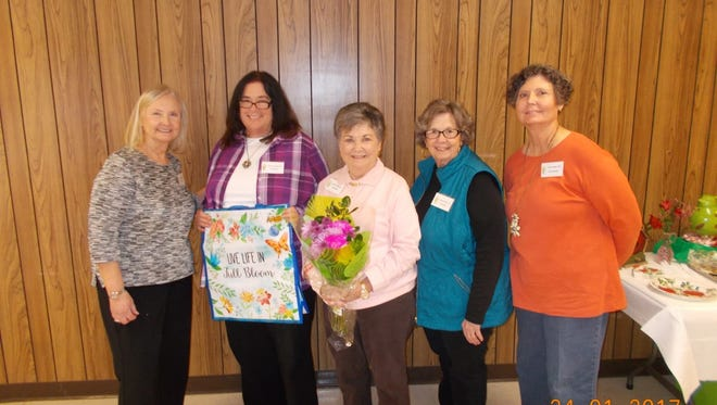 Shown from left are Ellen Waters, hostess; Judy Rains with theme tote prize; Joyce Mathis with flowers; and Judy Hulsey and Phyllis Mauldin, both hostesses.