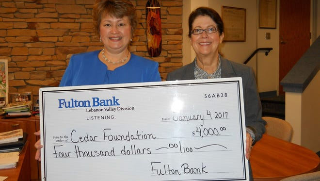 Rebecca Witherite (left), vice president of commercial lending for Fulton Bank, presents Lebanon School District Supt. Marianne Bartley with a replica check for $4,000 representing the bank's recent donation to the Cedar Foundation.