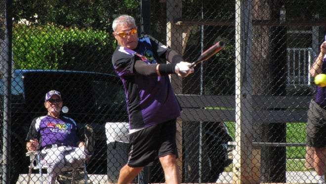 Rookies manager Tom Loiacono slashes a base hit as coach Ron Irwin looks on with approval.