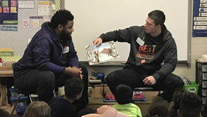 Shown are Clemson University football players, Christian Wilkins and Garrett Williams as they read to a kindergarten class at Ravenel Elementary School.