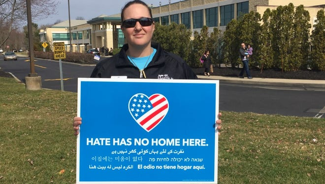 AJ Greenetz, a fitness instructor at Katz Jewish Community Center in Cherry Hill, holds an anti-hate sigh after a bomb scare Monday.