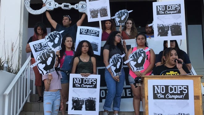 """More than a dozen students held up signs in support of the """"#CopsOuttaCampus"""" campaign on Thursday evening in central Phoenix."""