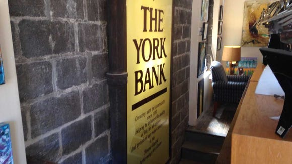 An old York Bank sign hangs in i-ron-ic. It's among
