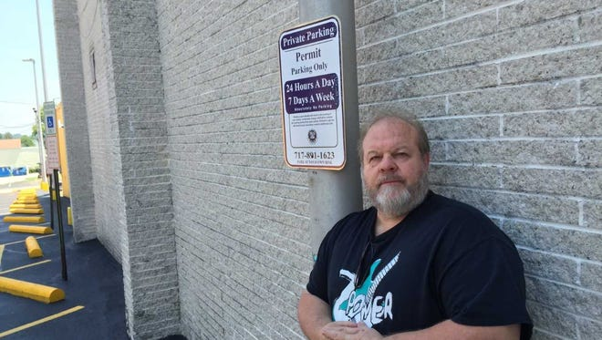 Business owner and North York Mayor Jerry Duncan stands in front a sign in the parking lot next door to his business warning that unauthorized vehicles will be booted. Previously, his customers could park in the lot. But new owners changed that.