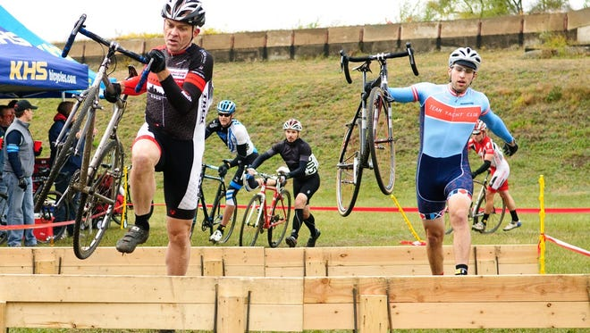 Tim Faas, left, and other cyclists maneuver an obstacle course during a cyclocross event.