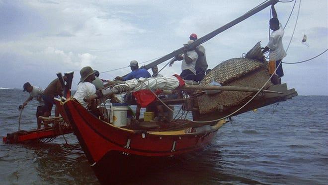 "In this 2003 file photo, master navigator ""Papa Mau"" Piailug and his crew make a trip from Gachpar, Yap, to Melekeok, Palau."